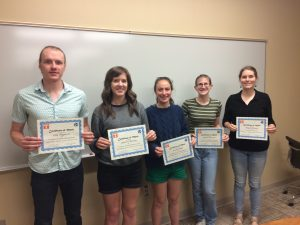 Students hold their Certificates of Merit in honor of their efforts in teaching, outreach, and research.