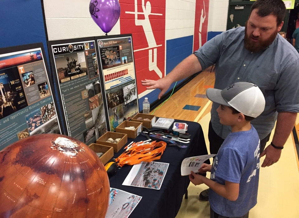 Undergraduate student explains STEM display to elementary student